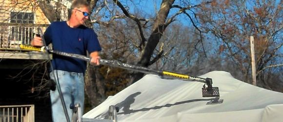 Peter Chappell leaning over a boat to shrink the plastic shrink wrapping material with heat gun