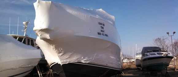 photo of a boat with white shrink wrapping covering it. An example of a service offered.